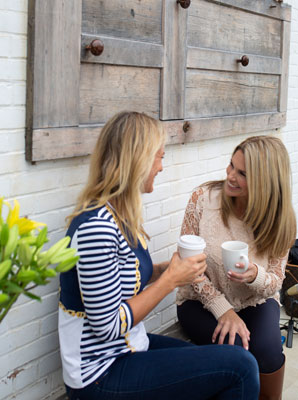 Dr. Krista Wells talking with a woman both drinking coffee